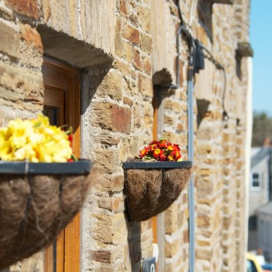 Flower baskets on house in Camelford